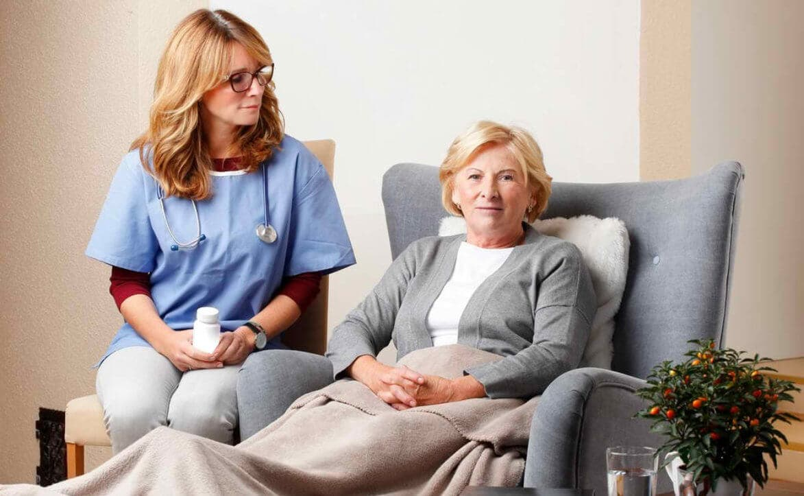 Portrait of smiling home caregiver sitting with senior patient