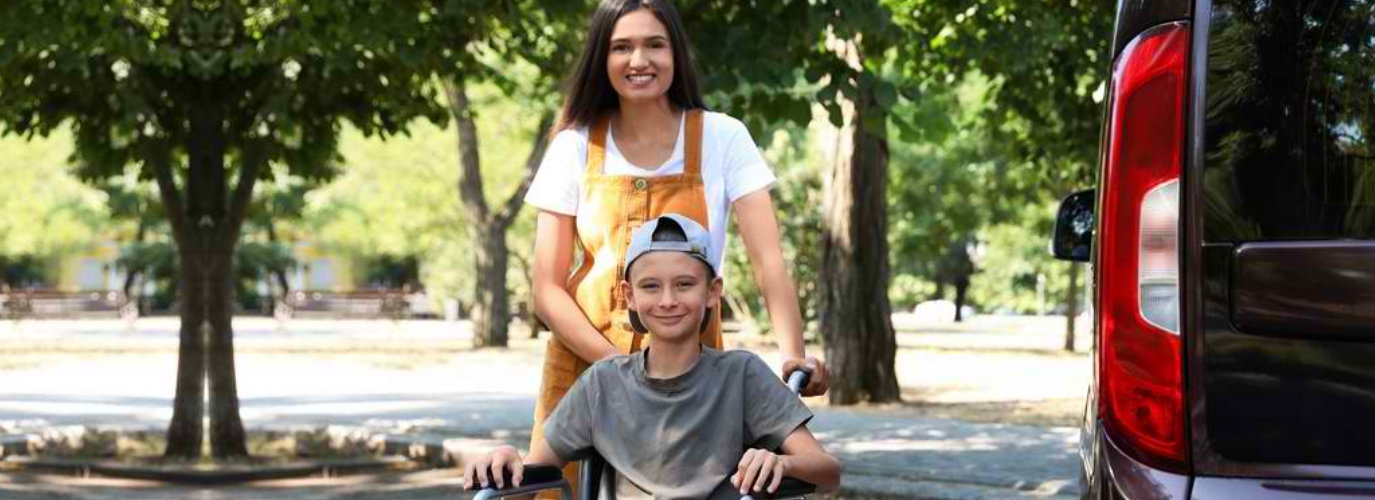 woman and a boy in a wheelchair smiling